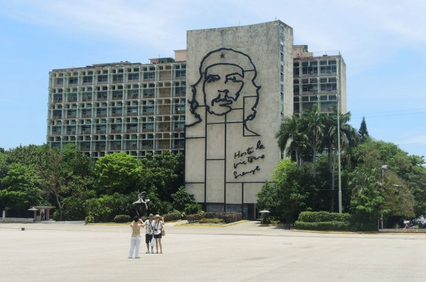 A multi storey apartment building. On the side is a very large outline drawing of Che Guevara's head and the words Hasta la victoria siempre
