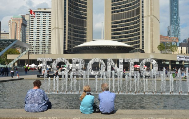 Three people sit on the bench beside the fountain at Nathan Phillips Square. Their backs are to the camera, they are looking towards the 3D Toronto sign that is covered with black and white photos for Inside Out project. Toronto city hall is in the background