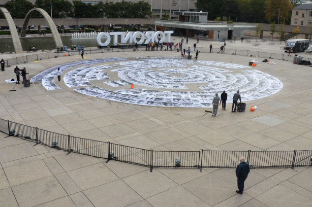 Concentric circles of black and white photos are being glued to the concrete at Nathan Phillips Square, overview, photo taken from the upper level.