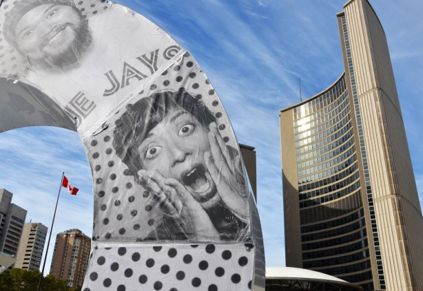 Two photos that are glued on the O of the 3D Toronto sign. One is of a man in Blue Jays T shirt and one is of a ayoung man with his hands on his cheeks and a wide eyed, open mouthed look of astonishment on his face. Toronto city hall is in the background