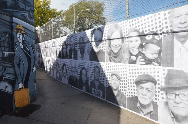 exterior concrete wall covered with black and white photos of people
