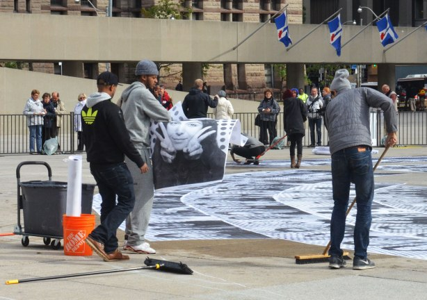 A group of young people are using brooms and sqeegees to glue blackand white photos of peoples faces onto the concrete of Nathan Phillips Square