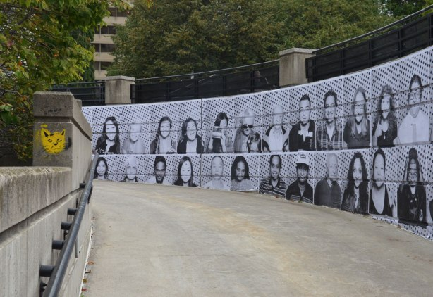 A wall alongside a sidewalk ramp is covered with black and white photos of people's faces.