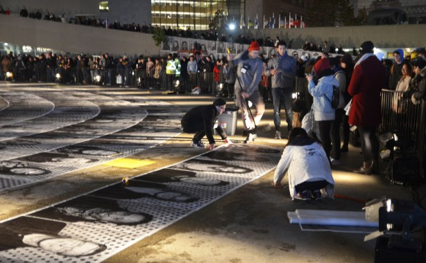 a group of people is gluing pictures to the concrete while many people look on, most are behind barricades, night time