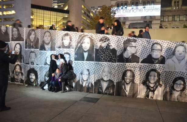 A group of people pose beside a wall that is covered with pictures, nuit blanche, night time.