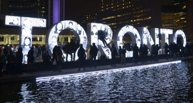 3D Toronto sign covered with black and white pictures of people, at night, at Nuit Blanche when there were a lot of people standing around it.