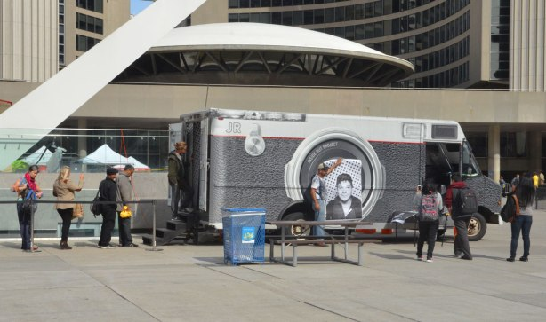 A picture of the mobile photoprinting booth that was used for the Inside Out global art project at Nathan Phillips Square. Some people are waiting in line to have their picture taken.