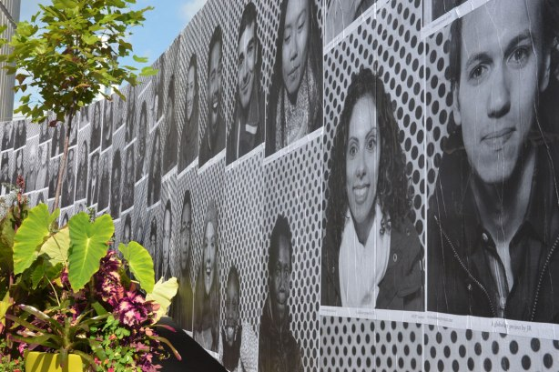 black and white photos of peoples faces glued to a wall, part of Inside Out Project in Toronto