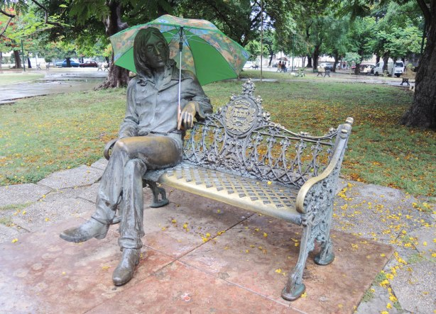 A statue of John Lennon sitting on a park bench in Havana. He's holding a green umbrella in the rain.
