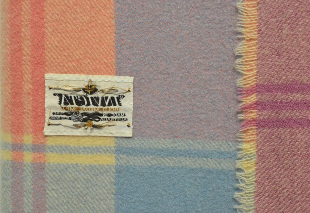 The label on a plaid blanket is sewn on backwards so that the writing on the label faces the blanket.