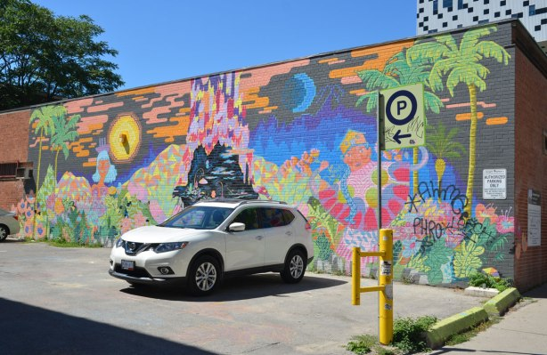 mural on the side of low building, beside w parking lot with one white car parked there.