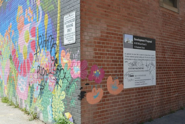 corner of a red brick building with a mural on one side and a standard city of Toronto black and white development proposal sign on the other.
