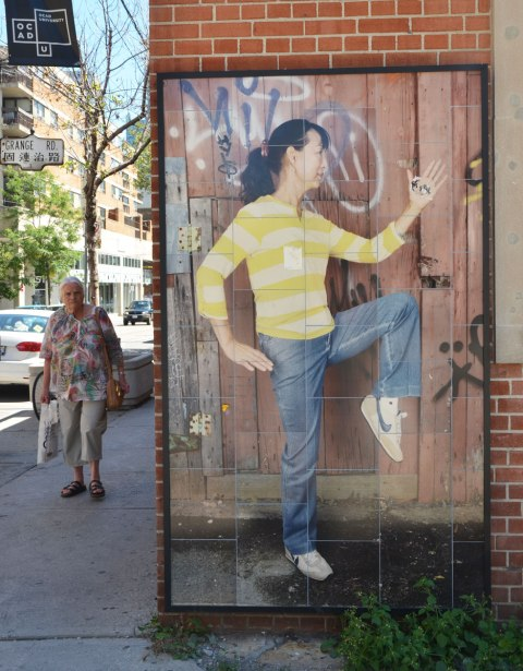 A picture of a woman in profile, with one knee raised, wearing a yellow and white striped top, picture on a wall. An older woman is walking on the sidewalk, approaching the camera.
