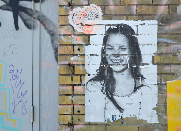yellowish brown brick wall with a wheatpaste of a girl with long hair and eyes closed. Above her is a paper lace doillie in a heart shape. Part of a grey metal door is also in the picture