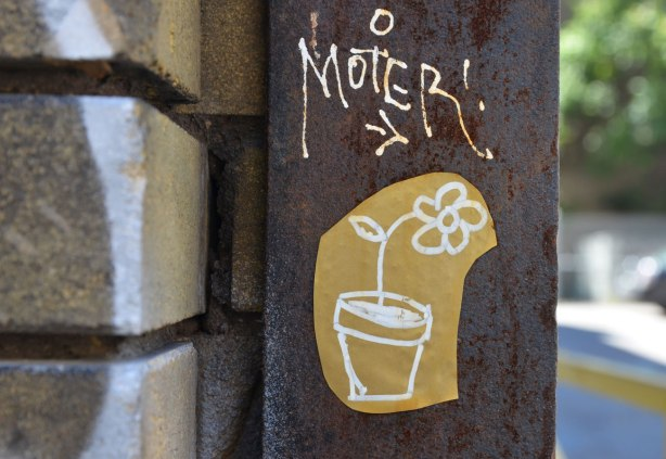 on a rusty metal pole beside a brick wall, close up of a flower in a flower pot line drawing in white on brown paper with the word moter in white above it with an arrow pointing to the flower