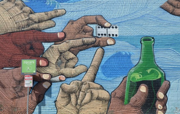 close up of bottom left of a mural showing 7 hands of different shades of brown and beige. One is holding a pair of dice (two sixes), one is holding a green bottle, presumably with alcohol in it, the other fingers are pointing to the right, towards the main part of the mural.