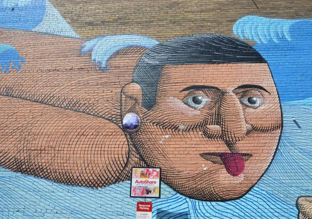 street art mural, close up of part of it, showing a man swimming in wavy water, he has short black hair, a shiny round ear ring, and his tongue is sticking out. his arms are at his side.