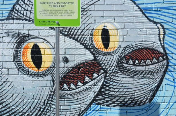 two big round grey fish with open mouths and big yellow eyes, part of a larger mural