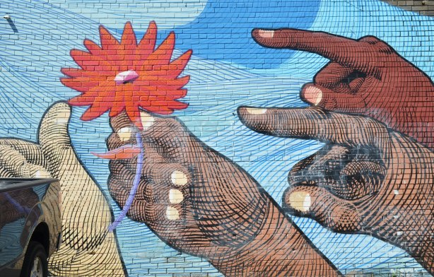 part of a mural by Nunca, four hands of differing shades of brown and beige are pointing or holding a large orange flower
