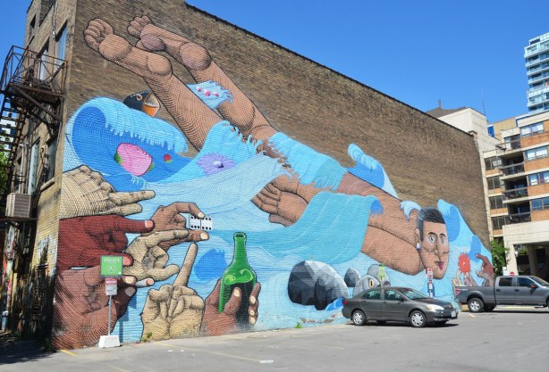 large mural on an exterior wall beside a parking lot. A man is swimming away from hands holding booze and dice and towards hands holding flowers. There are a few fish in the water with him. Painted by street artist Nunca on a bulding on McCaul Street in Toronto
