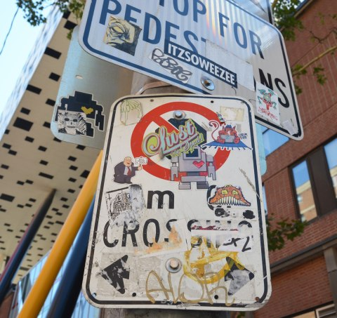 street signs covered with stickers and slaps in front of OCAD University