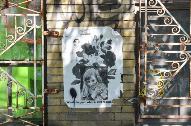 wheatpaste of a girl holdinging something, with poppies behind her, on a brick wall, with decorative metal grilles on either side of her