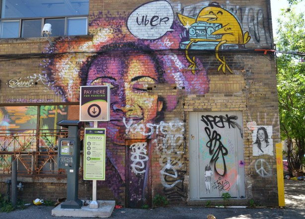 street art piece of a woman's face with eyes closed and a vague shape of a heart behind her, done in purples and yellows, by Dasic Fernandez, on the side of brick building, with a pay machine for a parking lot in front of it. Just above her is an UBER5000 birdie with a ghetto blaster