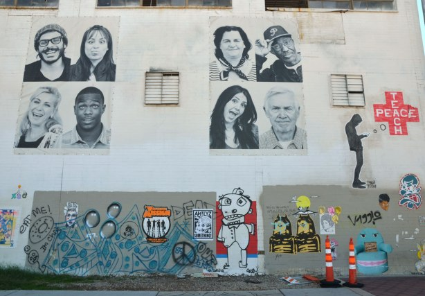 eight large black and white photos of people from the shoulders up on the upper level of a building wall. On the lower level is some graffiti and street art.