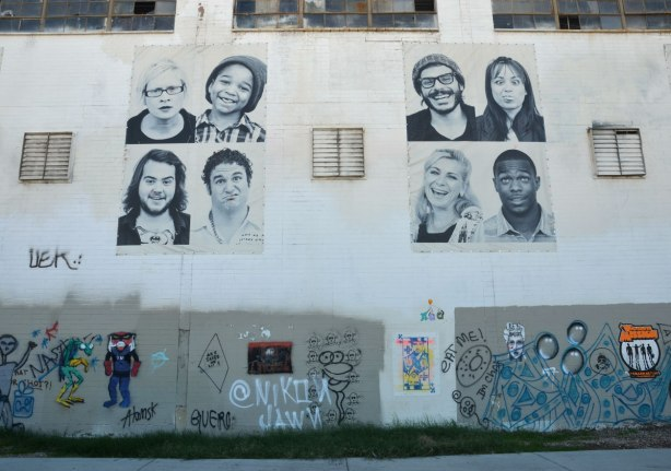 eight large black and white photos of people from the shoulders up on the upper level of a building wall. On the lower level is some graffiti and street art. Inside Out Global Art Project