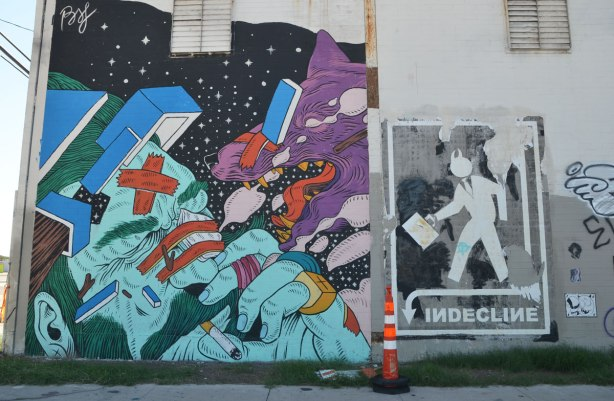 a mural and a wheatpaste. The mural is a green and light blue man's head, fingers by his face, cigarette in his mouth. A purple dog is lunging at him with its mouth open. The wheatpaste is a silhouette man carrying a briefcase with the word indecline written below him.