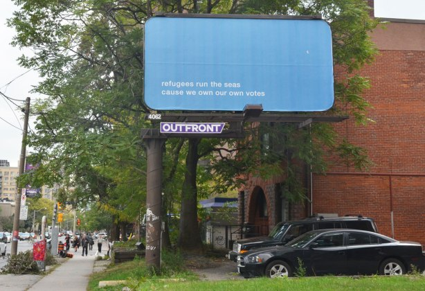 a billboard on a city street. it is blue with just the words on it that say Refugees run the seas cause we own our own votes