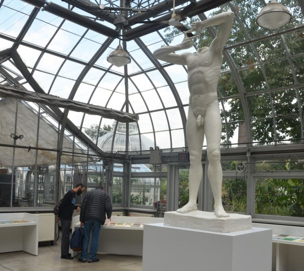 In a glass walled and glass roofed conservatory, a white statue of a headless naked man stands on a pedestal in the middle of the room. Two men are looking at a display on a table in the left of the picture.