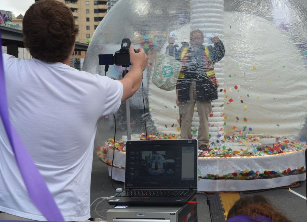 A man stands inside a large clear plastic bubble with many bits of coloured paper. He is posing for a photograph. In the foreground is part of the back of the photographer, his camera, and the laptop showing the photo.