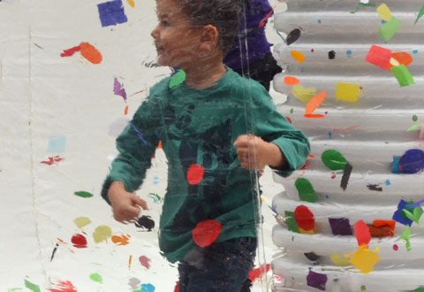 A boy stands inside a large clear plastic bubble with many bits of coloured paper. He is batting at the papers and smiling.