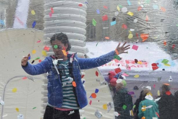 A woman stands inside a large clear plastic bubble with many bits of coloured paper. She is posing for a photograph.