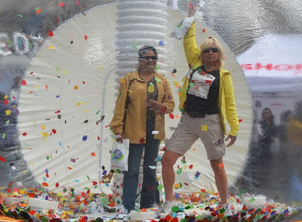 Two women stand inside a large clear plastic bubble with many bits of coloured paper. They are posing for a photograph.