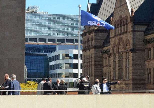 The blue flag of CARP (Canadian Association of Retired Persons) flies in front of Toronto city hall during the official flag raising ceremony.