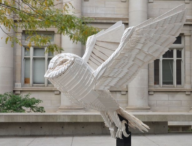 sculpture of a barn owl taking flight made of white lego, on a black pedestal (also made of lego) in front of the gardiner museum