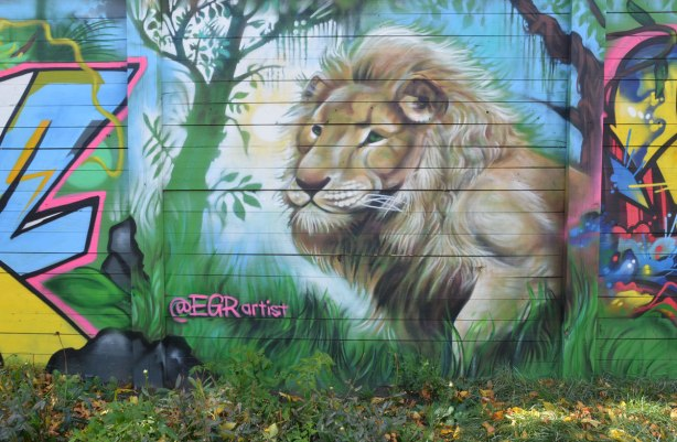 street art mural by EGR of a lion beside a tree