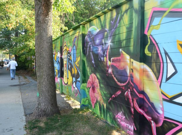 side view of a street art mural on a wall beside a sidewalk, the closest part of the mural is a picture of two giant beetles by Nick Sweetman with a painting of a spray paint can farther down the fence.