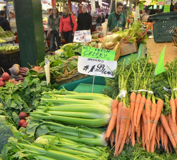 carrots and celery for sale in the foreground, market in the background with people, banasa, and other veg and fruit for sale