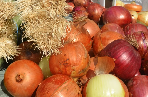 different kinds of onions as well as leeks for sale at an outdoor market