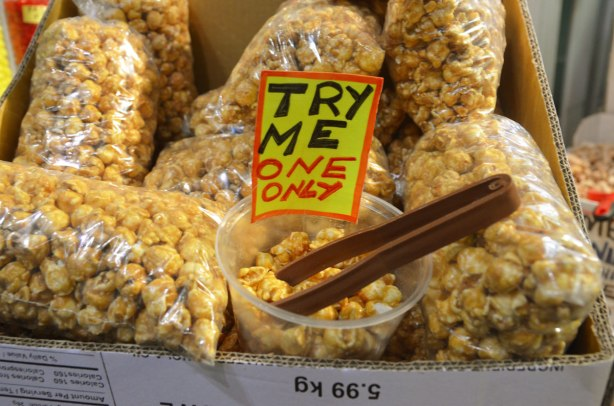 caramel popcorn for sale in bags as well as a small container of samples with a sign that says try me one only