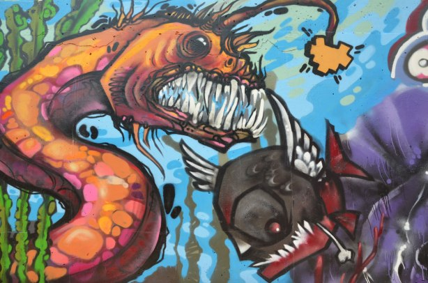 part of a larger mural painted on the side of an underpass - a water serpent, or an eel, with big teeth is after a smaller black fish