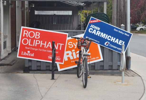 Three federal election campaign signs outside a restaurant, one each for the Liberals, Conservatives and NDP