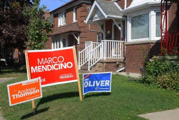Three federal election campaign signs on a front yard, one each for the Liberals, Conservatives and NDP