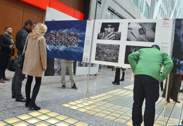 Three people are looking at a series of photographs on display. One of the photos is a boat carrying refugees, taken from above, the boat is packed full