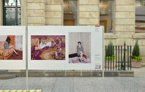 Three pictures on white board on display in the Allan Lambert gallery in Brookfield Place. Behind the board is the stone facade of the old bank building.