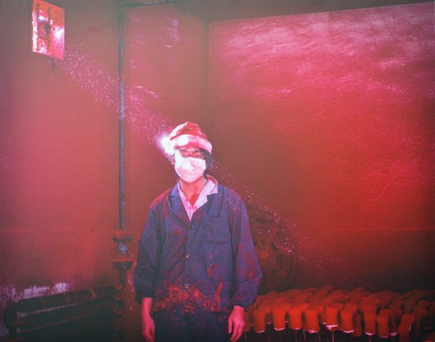 A picture of a photograph taken in a red room of a young man wearing a Santa Claus hat and a blue jacket.