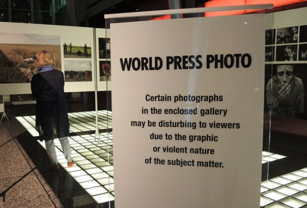 World Press Photo contest winners, sign cautioning people that the section they are about to enter has some disturbing images in it.